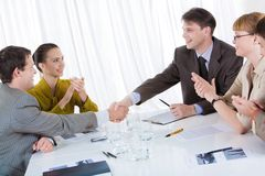 Making a deal. Business partners shaking hands after striking deal while their co-workers applauding royalty free stock photography