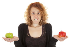 Making a decision. An attractive young woman offers a red and green apple royalty free stock photos