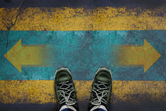 Making Decision Concept, Top view of Male with Casual Adventure. Shoes with Arrow Left and Right present over Grunge Cement Concrete Crossroad Background Royalty Free Stock Image