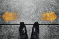 Making Decision Concept, Top view of Male with Oxford Business s. Hoes with Arrow Left and Right present over Grunge Cement Concrete Crossroad Background Stock Image