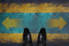 Making Decision Concept, Top view of Male with Oxford Business s. Hoes with Arrow Left and Right present over Grunge Cement Concrete Crossroad Background Stock Images