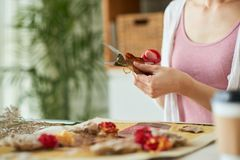Making Decor Item at Home. Unrecognizable woman wearing top and cardigan using scissors while making decor item from withered leaves and flowers at home Royalty Free Stock Images