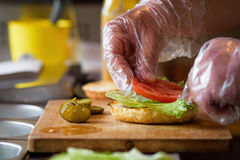 Making Delicious Homemade Maxi Burger with grilled beef steak, lettuce, cheese, tomato, onion, barbecue sauce, honey mustard, pick Royalty Free Stock Image