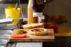 Making Delicious Homemade Maxi Burger with grilled beef steak, lettuce, cheese, tomato, onion, barbecue sauce, honey mustard, pick Stock Photo