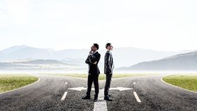 Making desicion or choosing the side. Mixed media. Two businessmen standing back to back and looking away. Mixed media Royalty Free Stock Images