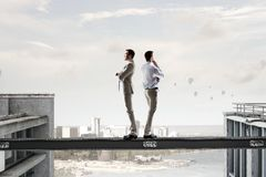 Making desicion or choosing the side. Mixed media. Two businessmen standing back to back and looking away. Mixed media Royalty Free Stock Photos
