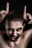 Making devil horns. Fun luxury woman making devil horns screaming on black background Royalty Free Stock Photo