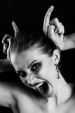 Making devil horns. Fun luxury woman making devil horns screaming on black background monochrome Stock Photos