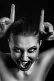 Making devil horns. Fun luxury woman making devil horns screaming on black background, monochrome Royalty Free Stock Photo