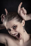 Making devil horns. Fun luxury woman vampire making devil horns screaming on black background Stock Photos