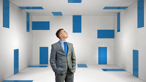 When making difficult decision. Businessman in room choosing one of plenty of doors Stock Photography
