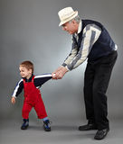 Making discipline. Grandfather trying to discipline his naughty grandson stock photos