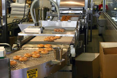 Making Donuts. Automated donut making machine with glazed donuts Stock Image