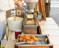 Making donuts. Demo cooking. Street food market. Vendors at the street market make fresh donuts. Small donut manufacture at street market. Demonstration cooking Stock Photo