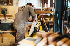 Making doors. Carpenter in uniform working with wooden plank Stock Images