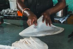 Making dough bread. Indian chef prepares a big cake. street food in India. make pancakes royalty free stock photos