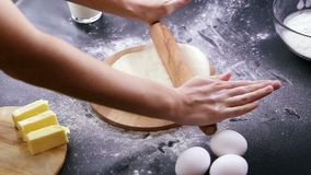 Making dough by female hands on wooden table background stock footage