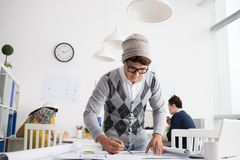 Making draft. Stylish Vietnamese architect making draft in the office Royalty Free Stock Photos
