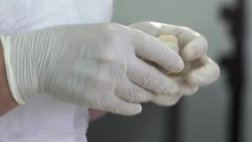 Making dumpling. Woman worker forming dumpling of dough and meat at meat factory. Making dumpling. Woman worker in white uniform and latex gloves forming stock footage