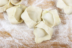 Making dumplings, raw pastry on wooden board. Royalty Free Stock Image