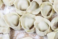 Making dumplings, raw pastry on wooden board. Stock Photo