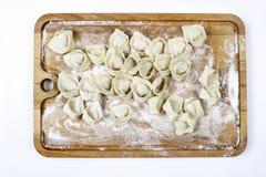 Making dumplings, raw pastry on wooden board. Stock Photos