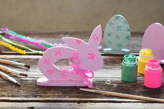 Making Easter decoration - easter eggs and bunny. Painting and coloring wooden toy of brushes and gouache. Creative process. Childrens DIY concept royalty free stock photography