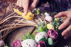 Making of Easter DIY wreath. With eggs and flowers, composition on rustic wooden table stock photos