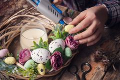 Making of Easter DIY wreath. With eggs and flowers, composition on rustic wooden table stock images