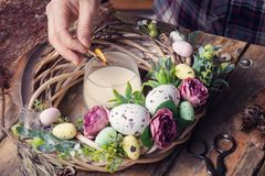 Making of Easter DIY wreath. With eggs and flowers, composition on rustic wooden table stock photo