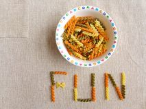 Make meal time fun for kids - concept. Making eating time a fun time for children - A bowl of raw uncooked ribbon farfalle italy pasta in a colourful alphabet Stock Photo