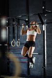 Making effort. Active young woman doing pull-ups Royalty Free Stock Photo