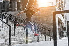 Making effort. Full length of handsome young man in sport clothing jumping while exercising outside Stock Photo