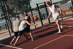 Making effort. Group of young men in sports clothing playing basketball while spending time outdoors stock image