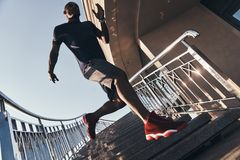 Making effort. Full length of young African man in sports clothing running down the stairs while exercising outdoors stock images