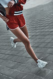 Making an effort to achieve her goal. Close-up of young woman in sport clothing running outdoors Stock Image