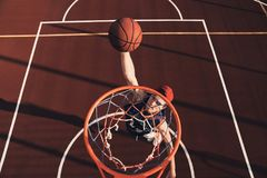 Making effort. Top view of young man in sports clothing scoring a slam dunk while playing basketball outdoors stock image