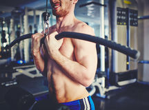 Making effort. Young man training on special sport equipment in gym Royalty Free Stock Images