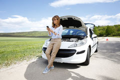 Making emergency call on the road. Full length portrait of confident middle aged woman using her mobile phone while standing on the road at her broken down car Royalty Free Stock Photo