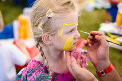 Making face-painting in action. Beautiful blond girl waiting to be face-painted royalty free stock photos