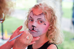 Making face painting of cat Stock Photo