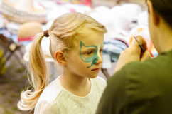 Making facepainting. Girl with long blond hair with facepainting stock photography