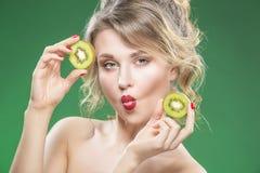 Making Faces di modello caucasico nudo divertente sensuale mentre posando con Kiwi Fruit succoso Immagine Stock