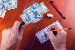 Making fake money. Drawing process of counterfeit money. On brown table royalty free stock photos