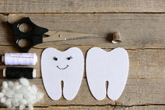 Making a felt tooth fairy toy. Step. On one side embroidered with black thread and beads eyes and mouth. Crafts supplies Royalty Free Stock Photography