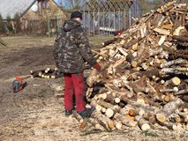 Making firewood 2. Man with axe and saw cutting firewood Royalty Free Stock Image