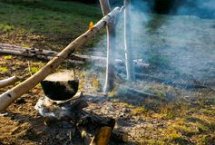 Making food in cauldron on fire. Steam and smoke all over the place stock photos