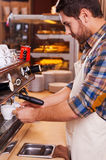 Making fresh coffee. Side view of confident barista making coffee while standing at the bar counter near the coffee machine Stock Photo
