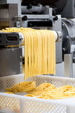 Making fresh Italian spaghetti pasta. With a close up view of the uncooked ribbons as they exit the automated cutting machine Stock Photo