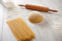 Making fresh spaghetti. Kitchen table with flour and dough spaghetti Royalty Free Stock Photos